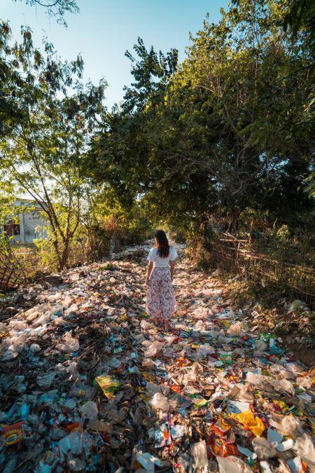 Foto de mujer de pie en una montaña de basura